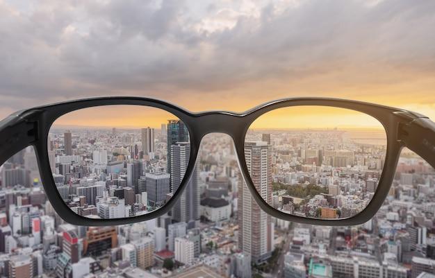 Olhando através de óculos para vista por do sol da cidade, focada na lente com fundo desfocado Foto Premium