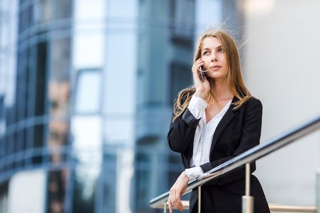 Olhando para longe mulher falando ao telefone Foto gratuita