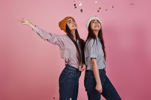 Olhando para o ar. concepção de ano novo. dois gêmeos jogando jogando confete dourado no ar Foto gratuita