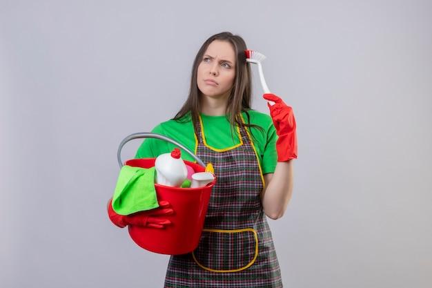 Olhando para o lado, pensando em limpar a jovem mulher usando uniforme com luvas vermelhas segurando ferramentas de limpeza, coça a cabeça com escova de limpeza na parede branca isolada Foto gratuita