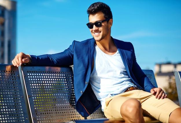 Olhar de alta moda. jovem elegante confiante feliz bonito empresário modelo homem em roupa de terno azul na rua, sentado num banco Foto gratuita