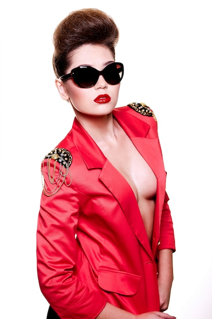 Olhar de alta moda. retrato de close-up de glamour sexy morena caucasiano feminino jovem com maquiagem brilhante com lábios vermelhos no casaco rosa brilhante em óculos de sol Foto gratuita