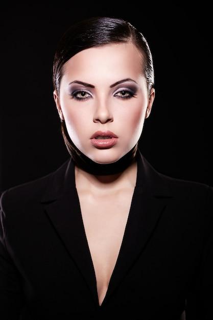 Olhar de alta moda. retrato do modelo de menina morena linda jaqueta preta com maquiagem brilhante e lábios suculentos. pele limpa. isolado no preto Foto gratuita