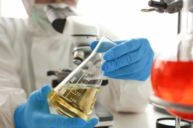 Olhar masculino do químico no tubo de ensaio da preensão do microscópio Foto Premium