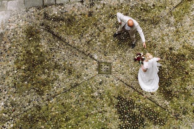 Olhe de cima para a noiva e o noivo andando pelo quintal Foto gratuita