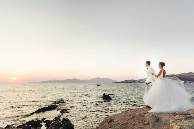 Olhe de longe no lindo casal de noivos assistindo o pôr do sol sobre o mar Foto gratuita