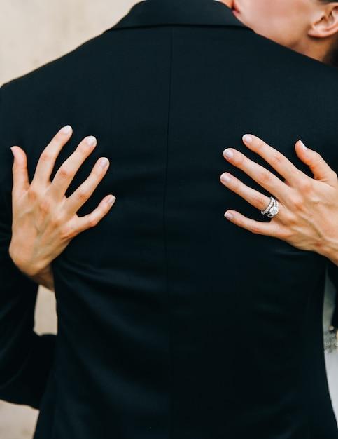 Olhe de trás na noiva que abraça a proposta do noivo. mãos no seu bac Foto gratuita