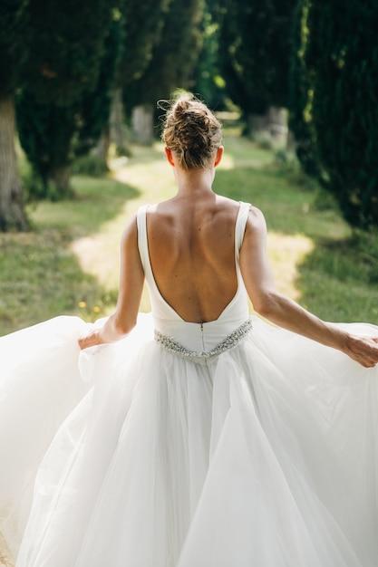 Olhe de trás para a noiva em vestido com as costas nuas correndo ao longo Foto gratuita