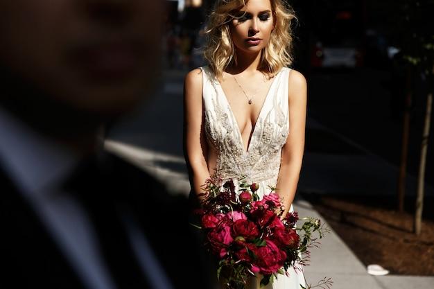 Olhe sobre o ombro do noivo na noiva de pé com o bouquet de casamento vermelho com luz do sol brilhante Foto gratuita