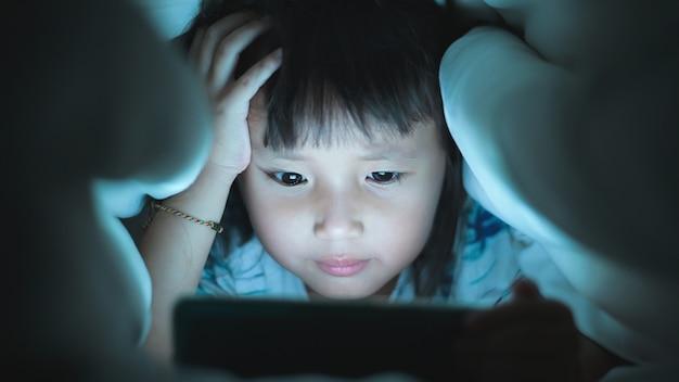 Olho de perto menina estão assistindo vídeo no tablet na cama durante a noite a luz pisca refletida na tela Foto Premium