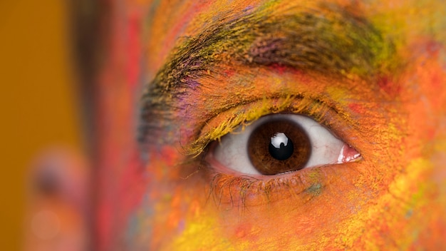 Olho marrom de jovem com maquiagem artística holi brilhante Foto gratuita