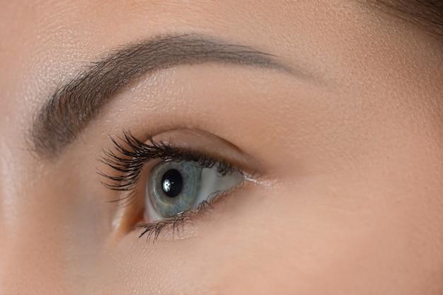 Olhos cinzentos de perto no rosto de uma jovem e linda garota caucasiana Foto gratuita