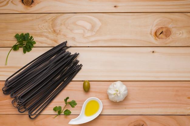 Oliva; alho; massa de arroz preto cru salsa e cru na mesa de madeira Foto gratuita