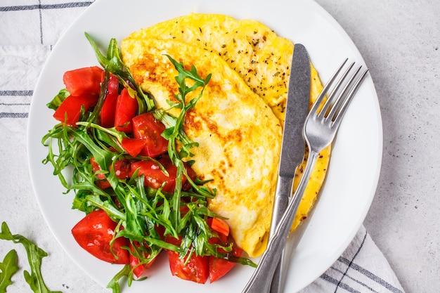 Omeleta clássica com queijo e salada dos tomates na placa branca, vista superior. Foto Premium