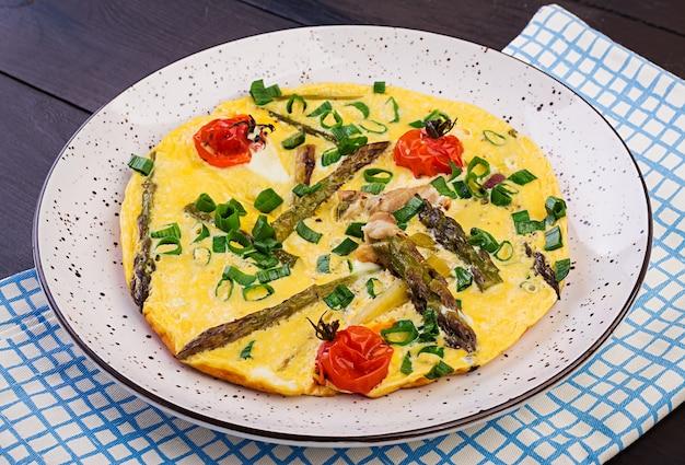 Omelete com espargos e tomate no café da manhã Foto Premium