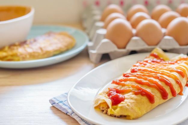 Omelete com ketchup no topo em um prato branco com uma bandeja de ovo borrão como pano de fundo Foto gratuita