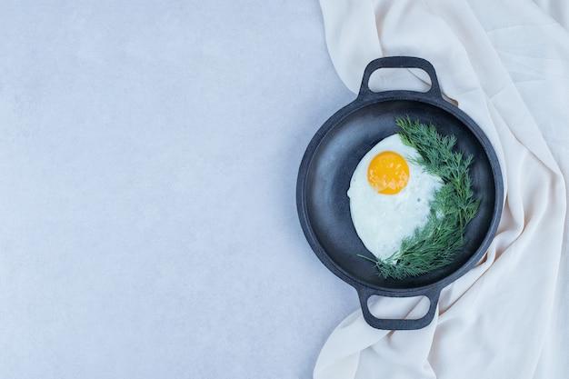 Omelete com pimenta na frigideira escura sobre branco Foto gratuita