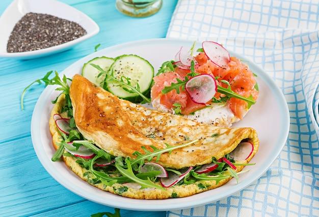 Omelete com rabanete, rúcula verde e sanduíche com salmão no prato branco Foto Premium