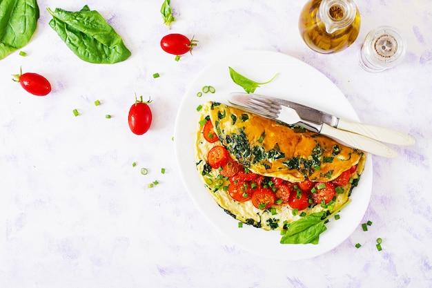 Omelete com tomate, espinafre e cebola verde na chapa branca. Foto Premium
