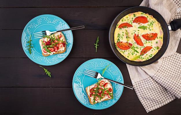 Omelete com tomate, presunto, cebola verde e sanduíche com morango na mesa escura, vista superior Foto Premium