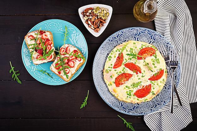 Omelete com tomate, presunto, cebola verde e sanduíche com morango na mesa escura Foto Premium