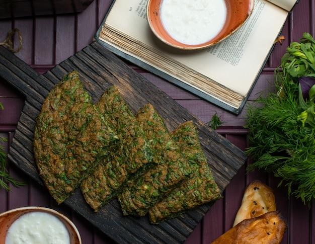 Omelete de ervas vegetais cortar fatias de pizza e servido com iogurte Foto gratuita