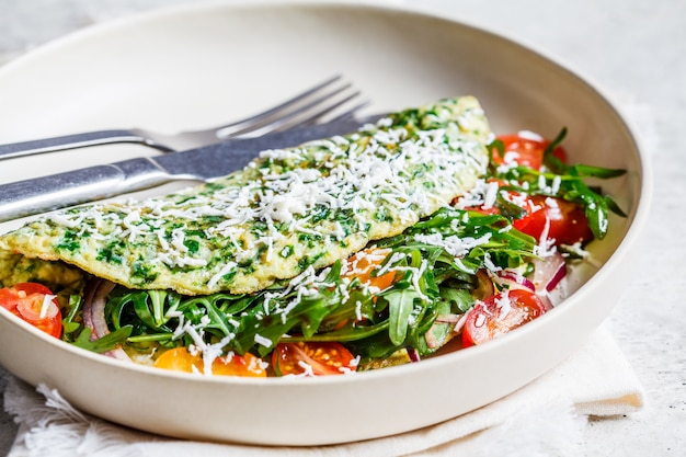Omelete de espinafre verde com queijo, rúcula e tomate em chapa branca. Foto Premium