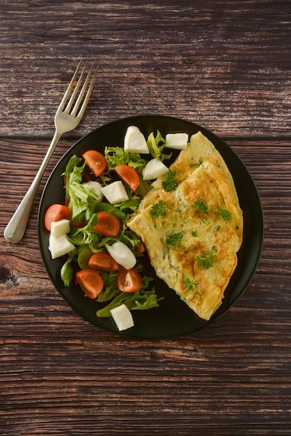 Omelete de ovo com tomate cereja, mussarela e salada verde. mesa de madeira com espaço de cópia. Foto Premium