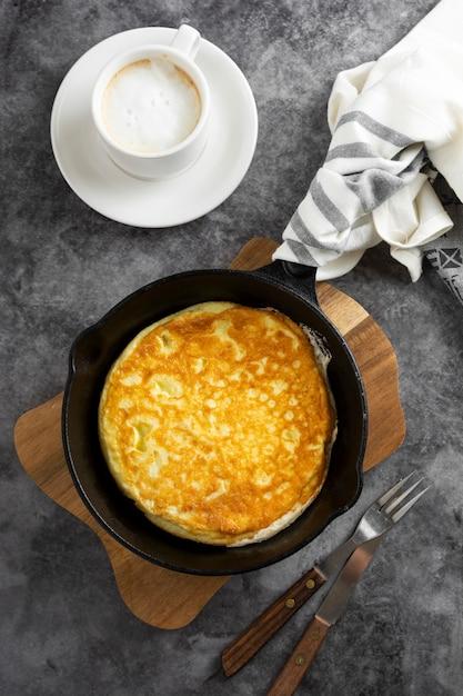 Omelete na frigideira e xícara de café. omelete saudável acabado de cozinhar. Foto Premium