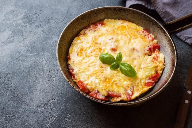 Omelete, ovos mexidos com tomate e queijo em uma panela sobre uma mesa escura. Foto Premium