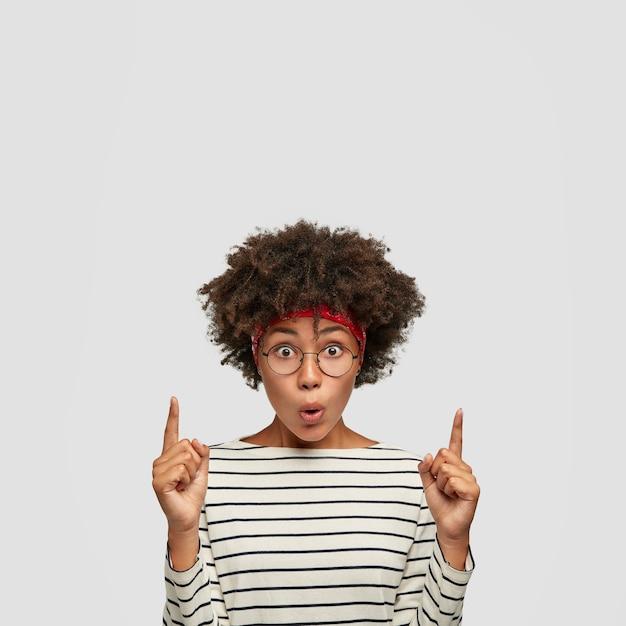Omg, algo acontece lá. adolescente emocional estupefato com pele escura, penteado afro Foto gratuita