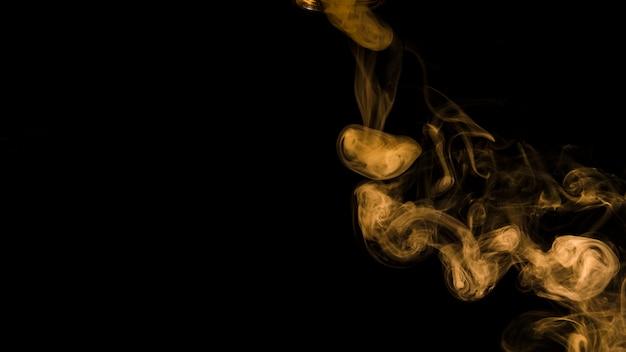 Onda amarela do fumo no fundo preto com espaço da cópia para escrever o texto Foto gratuita