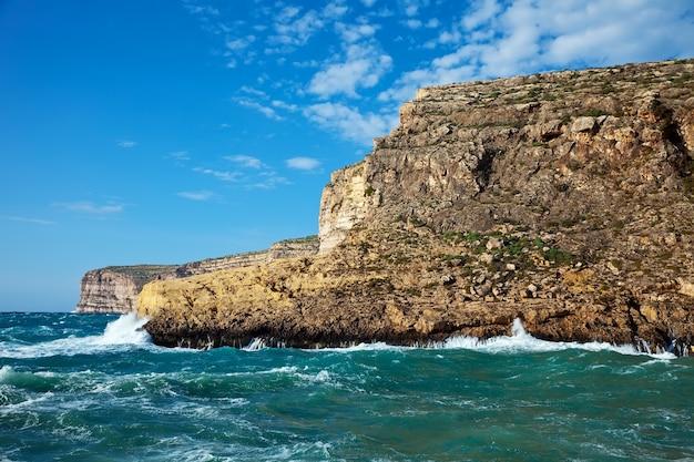Onda do mar que quebra contra o penhasco da costa Foto gratuita