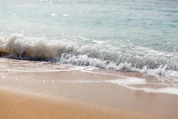 Onda espirrando em uma praia. fechar-se Foto Premium