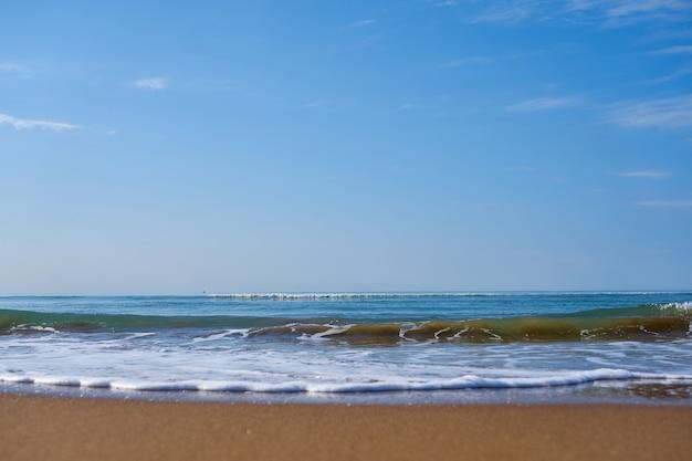 Ondas com espuma na praia arenosa do mar mediterrâneo indo além do horizonte Foto Premium