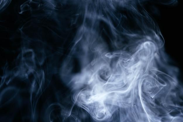 Ondas de fumaça azuis em fundo preto Foto gratuita