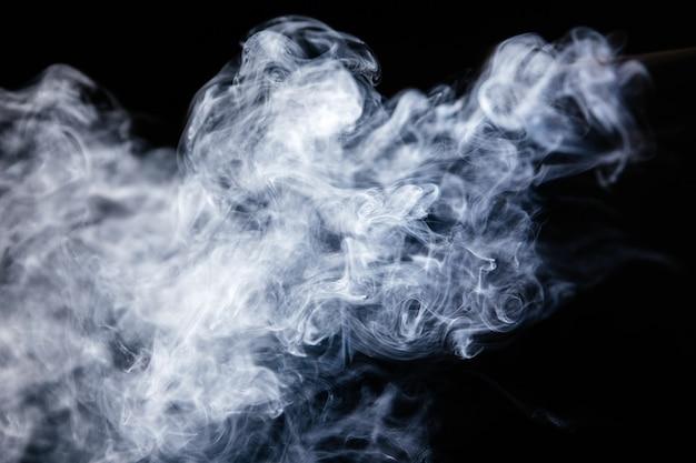 Ondas de fumaça cinza em fundo preto Foto Premium