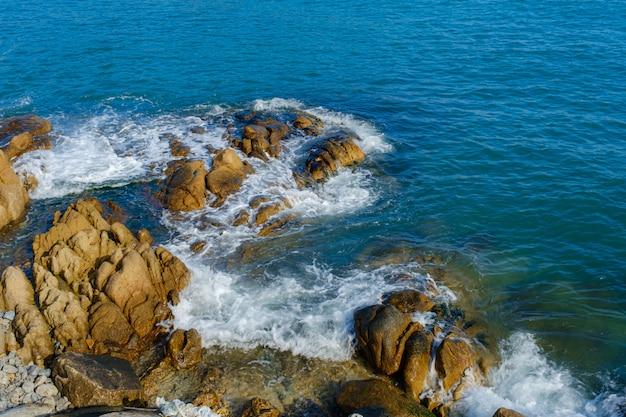 Ondas do mar espirram nas rochas Foto Premium