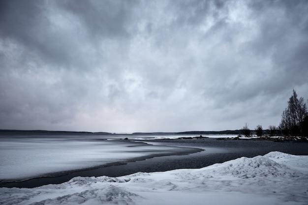 Ondas do mar se movendo em direção à costa sob o céu sombrio Foto gratuita