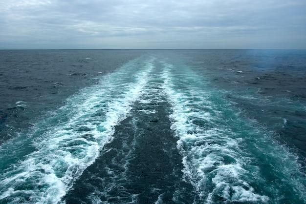 Ondas espumosas na superfície da água atrás do navio de cruzeiro Foto gratuita