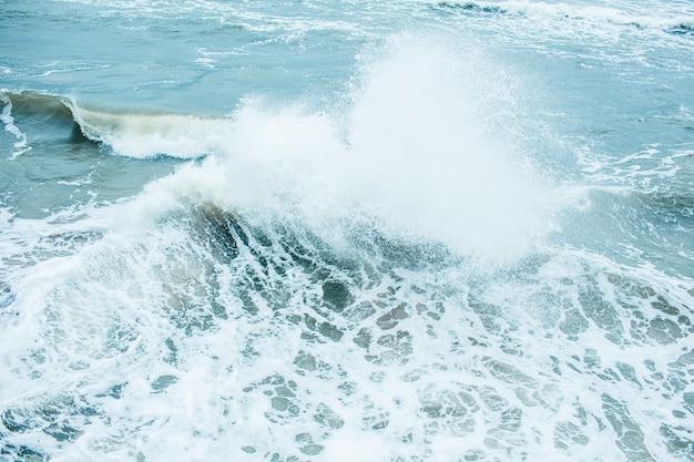 Ondas quebrando e pulverizando em alto mar e ventos fortes. ataque no mar no outono dia nublado chuvoso. Foto Premium