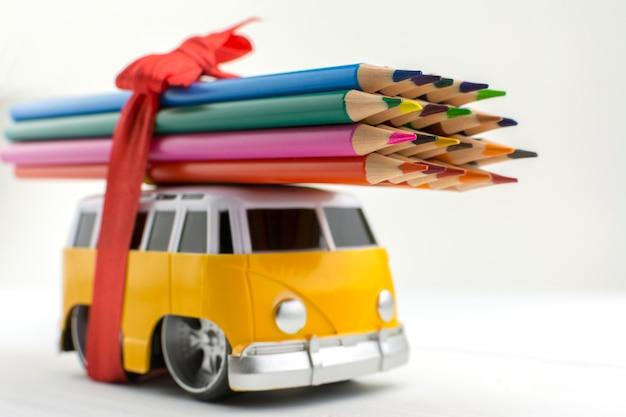 Ônibus de brinquedo carrega um monte de lápis de cor no telhado Foto Premium