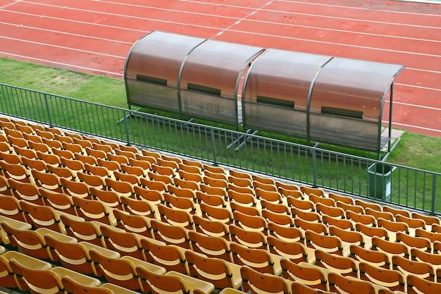 Ônibus e bancos de reserva com assentos amarelos no estádio de futebol Foto Premium