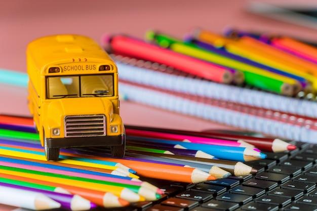 Ônibus escolar em lápis de cor e teclado, de volta à escola Foto Premium