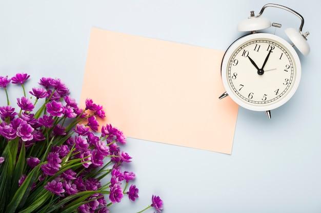 Op ver flores com cartão e relógio ao lado Foto gratuita