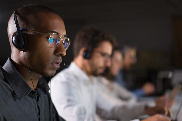 Operador de call center concentrado em comunicação com o cliente Foto gratuita