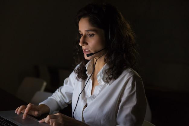 Operador de centro de chamada grave no escritório escuro Foto gratuita