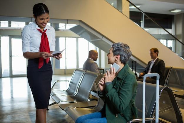 Operador de check-in da companhia aérea verificando passaporte na área de espera de check-in Foto gratuita