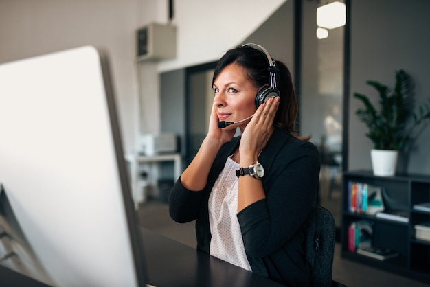 Operador de helpline feminino sorridente com fone de ouvido. Foto Premium