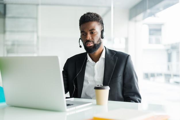 Operador de linha direta. retrato do representante de serviço ao cliente africano alegre com fone de ouvido em call center Foto gratuita